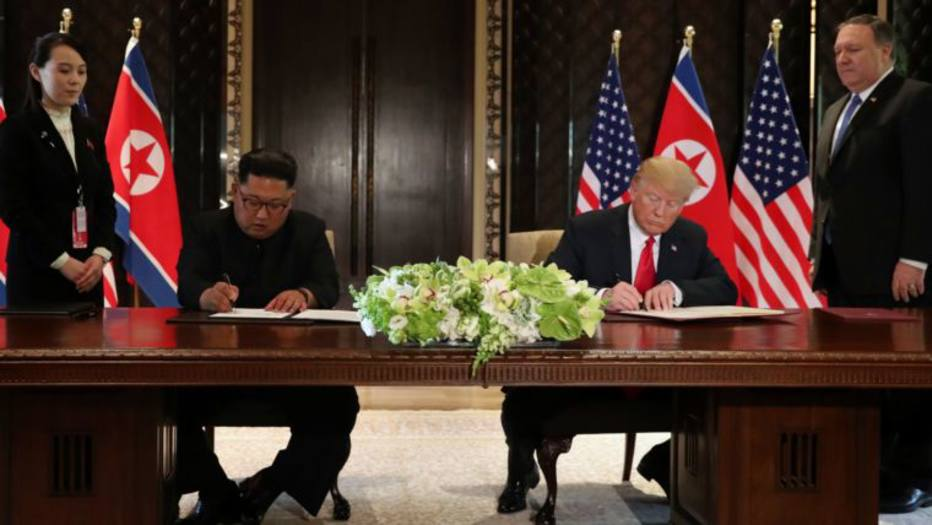U.S. President Donald Trump and North Korea's leader Kim Jong Un sign documents that acknowledge the progress of the talks and pledge to keep momentum going, after their summit at the Capella Hotel on Sentosa island in Singapore June 12, 2018. As they are watched by Kim Yo Jong, sister of North Korean leader Kim Jong Un and U.S. Secretary of State Mike Pompeo. REUTERS/Jonathan Ernst